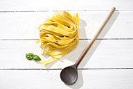 Fresh Pappardelle classico, leaves of basil, wooden spoon and flour on white wooden table - MAEF008080