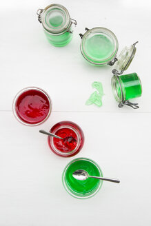Preserving jars of cherry and woodruff jelly on white ground, elevated view - LVF000782