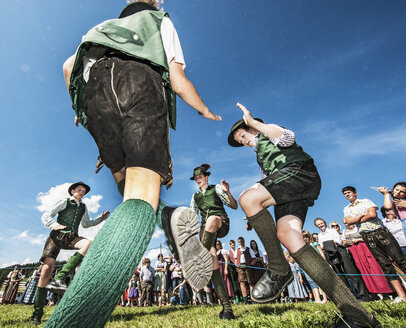 Austria, Irdning, Boys in traditional clothing dancing the Schuhplattler at May festival - HH004763