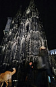Passers-by and dog at the Cologne Cathedral at Night, Cologne, North Rhine-Westphalia, Germany, - JAT000701