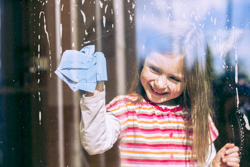 Portrait of smiling ittle girl cleaning window - SARF000312