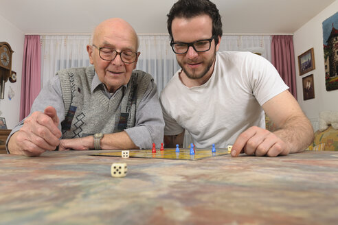 Grandfather and grandson playing together ludo at home - LA000662