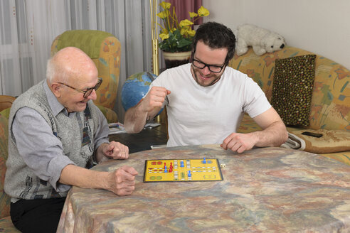 Grandfather and grandson playing together ludo at home - LA000650