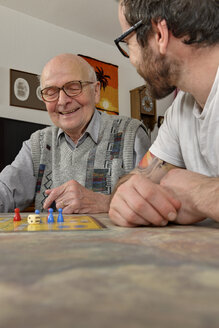 Grandfather and grandson playing together ludo at home - LA000665