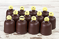Chocolate marshmallows decorated with different smiley faces on wooden table - CSF020943