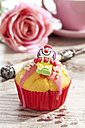 Decorated muffin in muffin paper on laid table - CSF020949