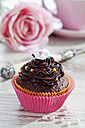 Decorated chocolate muffin in muffin paper on laid table - CSF020958