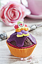 Decorated chocolate muffin in muffin paper on laid table - CSF020961