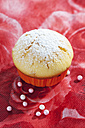 Muffin in muffin paper and sugar beads on red floral design - CSF020970