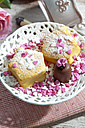 Two decorated muffins, chocolate marshmallow and sugar hearts on plate - CSF020994