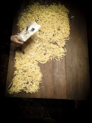 Putting flour on self made noodles on wooden table, Berlin, Germany - FB000342