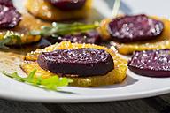 Grilled beetroot on orange slice, rocket and balsamico on plate - SARF000333