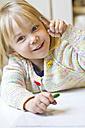 Portrait of smiling little girl showing finger full of colour - JFEF000272