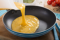 Liquid egg for a frittata is being poured into frying pan - CSTF000130