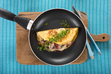 Omelette with champignon, onion and ham in frying pan - CSTF000161