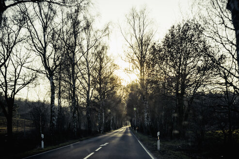 Germany, Mecklenburg-Western Pomerania, Ruegen, empty country road at sunset in winter - MJF000905