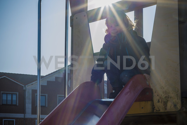 Germany, Mecklenburg-Western Pomerania, Ruegen, little boy sitting on shute in backlight - MJF000957