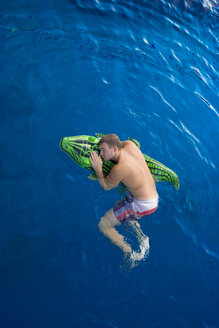 Young man with swim toy floating in water, view from above - PAF000552