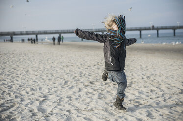 Germany, Mecklenburg-Western Pomerania, Ruegen, little boy running on beach in winter - MJF000946