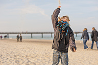 Germany, Mecklenburg-Western Pomerania, Ruegen, little boy on the beach throwing sand up in the air - MJ000947