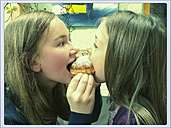 Teenage girl and girl bite together in a donut, Schirmitz, Bavaria, Germany - SARF000349
