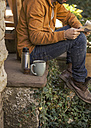 Young man sitting on steps having coffee break, partial view - EBSF000082