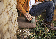 Young man sitting on steps having coffee break, partial view - EBSF000084