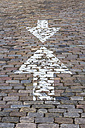 Germany, Bremen, Opposing arrow signs on cobblestone pavement - NKF000067