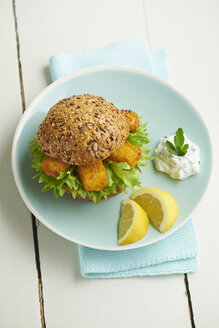 Burger with fish fingers and herb curd on plate - ECF000451