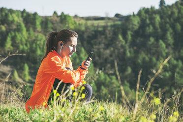 Spain, Catalunya, Orista, young female jogger having a break using smartphone - EBSF000097