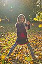 Little girl throwing autumn leaves in park - SARF000368