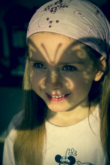 Portrait of little girl with butterfly-shaped shadow in her face - SARF000374
