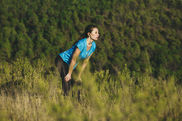 Young female jogger stretching in front of forest - EBSF000104