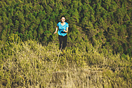 Young female jogger on the move in front of forest - EBSF000108