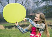 Germany, Landshut, Female teenager with green speech bubble - SARF000389