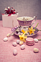 Laid table with cup, daffodils (Narcissus pseudonarcissus), macaron, sweets and gift - VTF000168