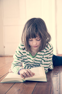 Portrait of little girl reading book at home - LVF000845