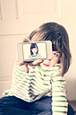 Little girl showing smartphone with self-portrait - LVF000888