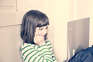 Portrait of little girl using laptop at home - LVF000898