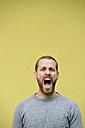 Portrait of screaming young man in front of yellow background - BR000170