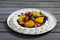 Meringue baked pastry case with chocolate icing garnished with  strawberries and peaches on paper plate and grey wood - CSF021046