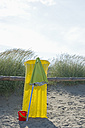 Italy, Adria, yellow air bed, basket and beach umbrella leaning at beach dunes - ASF005282