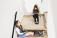 Two teenage girls sitting on stairs using smartphone and digital tablet - MAEF008277