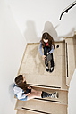 Two teenage girls sitting on stairs using smartphone and digital tablet - MAEF008280