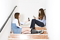 Two teenage girls sitting on stairs using smartphone and digital tablet - MAEF008283