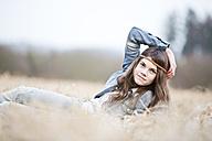 Portrait of teenage girl lying on field - MAEF008267