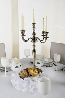 Laid table, white masks, bread basket and place settings - LRF000572