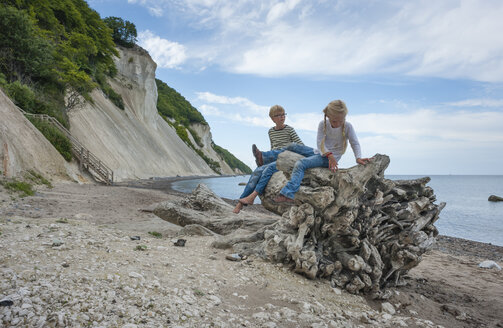 Denmark, Mon island, siblings playing below Mons Klint chalk cliffs - JBF000083
