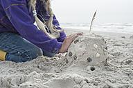 Denmark, Jutland, Vejers, girl building sandcastle - JBF000090