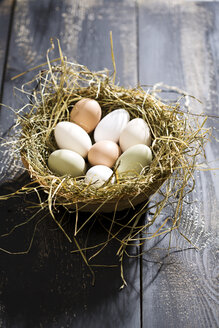 Easter nest with organic eggs on dark wood - MAEF008207